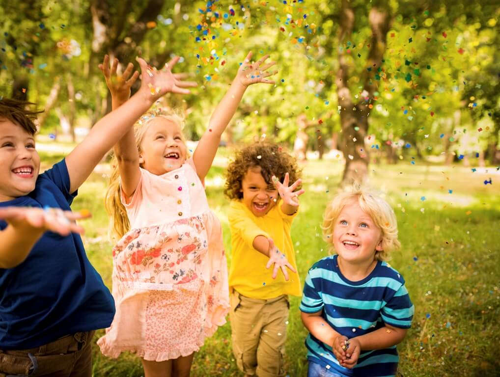 Happy child friends having fun with confetti in a park